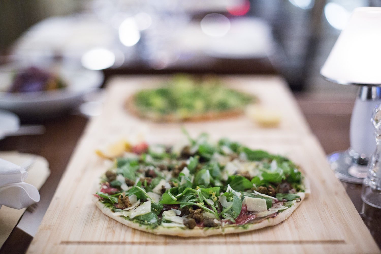 BEEF CARPACCIO FLATBREAD with herb mayo, arugula, crispy capers, lemon and parmesan