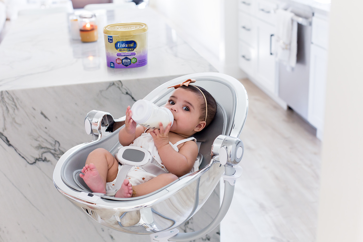 Baby holding her own bottle and drinking Enfamil formula